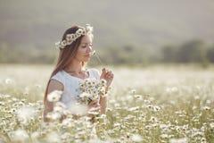 Piękna kobieta w wianku realów kwiaty z bukietem w polu białe stokrotki, Obrazy Royalty Free