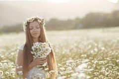 Piękna kobieta w wianku realów kwiaty z bukietem w polu białe stokrotki, Obraz Stock