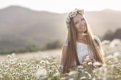 Piękna kobieta w wianku realów kwiaty z bukietem w polu białe stokrotki, Fotografia Stock
