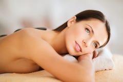 Piękna kobieta w zdroju salonie z gorącymi kamieniami Zdjęcia Royalty Free