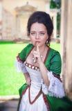 Piękna kobieta w zielonym średniowiecznym smokingowym robi cisza gescie zdjęcie stock