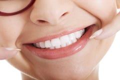 Piękna kobieta wskazuje na jej uśmiechu. obraz royalty free