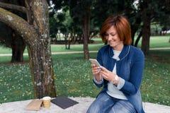 Piękna kobieta wysyła wiadomość na jej telefonie w parku Zdjęcie Royalty Free