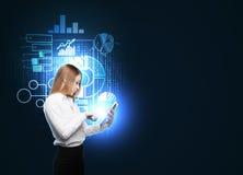 Piękna kobieta wyszukuje niektóre biznesowe mapy w pastylce Hologram biznesowe mapy latają nad kobietą Ciemny backgroun Zdjęcie Royalty Free