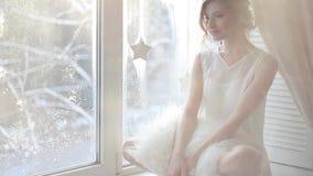 piękna kobieta z świeżym dziennym makeup i romantyczną falistą fryzurą siedzi przy windowsill, zbiory