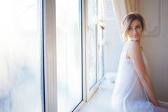 piękna kobieta z świeżym dziennym makeup i romantyczną falistą fryzurą siedzi przy windowsill, obrazy stock