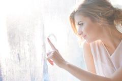 piękna kobieta z świeżym dziennym makeup i romantyczną falistą fryzurą siedzi przy windowsill, rysuje na szkle obrazy stock