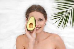 Piękna kobieta z avocado i tropikalnym liściem na białej tkaninie nad widok, zdjęcia royalty free