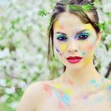 Piękna kobieta z barwioną farbą na twarzy plenerowej obrazy stock