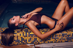 Piękna kobieta z ciemnym włosy w bikini pozuje w noc pływackim basenie Fotografia Stock