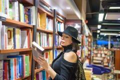 Piękna kobieta z czarnym kapeluszem jest w bookstore zdjęcia stock