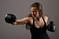 Piękna kobieta z czarnymi bokserskimi rękawiczkami fotografia royalty free