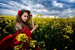 Piękna kobieta z czerwoną peleryną w żółtym kwitnienia polu Zdjęcia Stock