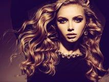 Piękna kobieta z długą kędzierzawego włosy i złota biżuterią zdjęcia royalty free