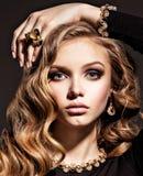 Piękna kobieta z długą kędzierzawego włosy i złota biżuterią zdjęcie royalty free