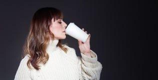 Piękna kobieta z długie włosy jest ubranym pulowerów chwytami tapetuje rozporządzalną filiżankę Pić kawę z zrelaksowaną profilową zdjęcia royalty free