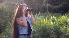 Piękna kobieta z długie włosy patrzeć przez lornetek Dziewczyna szpieg lub turysta Podróż i wycieczka zbiory wideo