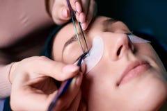 Piękna kobieta z długimi rzęsami w piękno salonie Rzęsy rozszerzenia procedura Baty zamykają up zdjęcia royalty free