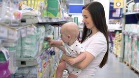 Piękna kobieta z dzieckiem na zakupach w supermarkecie, młoda matka wybiera jedzenie dla swojego dziecka na rynku zdjęcie wideo