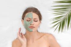Piękna kobieta z glinianą twarzową maską i tropikalny liść na białej tkaninie zdjęcie royalty free