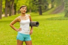 Piękna kobieta z joga matą outdoors Zdjęcie Stock