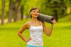 Piękna kobieta z joga matą outdoors, w parku Fotografia Royalty Free