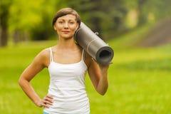 Piękna kobieta z joga matą outdoors, w parku Zdjęcie Royalty Free