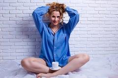 Piękna kobieta z kędzierzawego włosy rozciąganiem w łóżkowym cieszy się morni zdjęcia stock