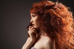 Piękna kobieta z kędzierzawym włosy na szarym tle Obraz Stock