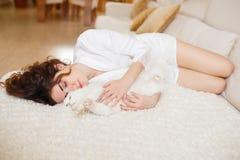 Piękna kobieta z kędzierzawym włosy w białej jedwabniczej opatrunkowej todze w ranku bawić się z białym puszystym kota obsiadanie Obraz Royalty Free