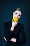 Piękna kobieta z kolor żółty róży kwiatem w jej usta Zdjęcie Royalty Free