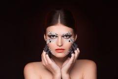 Piękna kobieta z kryształu makeup utrzymuje ona blisko stawiać czoło ręki Zdjęcie Royalty Free