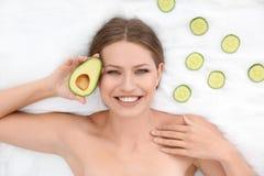 Piękna kobieta z ogórków plasterkami i avocado na białej tkaninie nad widok, zdjęcie royalty free