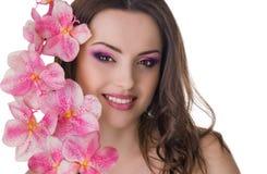 Piękna kobieta z orchideą wewnątrz słucha Obraz Stock