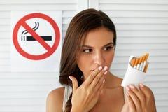 Piękna kobieta Z paczką papierosy I Palenie Zabronione znak zdjęcia stock