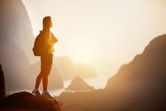 Piękna kobieta z plecakiem przy wschodem słońca lub zmierzchem na góra wierzchołku Zdjęcie Stock