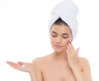 Piękna kobieta z ręcznikiem na głowie kremowa twarz Zdjęcia Stock