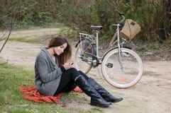 Piękna kobieta z rowerowym obsiadaniem w parku i patrzeć p Obrazy Stock