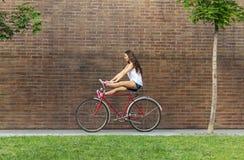Piękna kobieta z starym rowerem przed ściana z cegieł zdjęcie stock