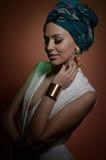 Piękna kobieta z turbanem Młoda atrakcyjna kobieta z turbanem i złotymi akcesoriami Piękno modna kobieta Fotografia Stock
