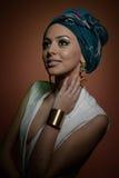 Piękna kobieta z turbanem Młoda atrakcyjna kobieta z turbanem i złotymi akcesoriami Piękno modna kobieta Fotografia Royalty Free