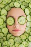 Piękna kobieta z twarzową maską ogórków plasterki na twarzy Zdjęcie Stock