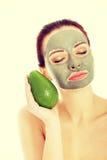 Piękna kobieta z twarzowym maskowym mienia avocado Zdjęcia Royalty Free