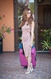 Piękna kobieta z walizkami opuszcza hotel w dużym mieście Atrakcyjna rudzielec z okularami przeciwsłonecznymi i elegancką suknią  Zdjęcie Stock