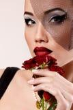 Piękna kobieta z zmrokiem - czerwone róże kwitną w przesłona retro splendorze Zdjęcie Stock