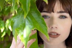 Piękna kobieta za zielenią opuszcza patrzeć kamerę obrazy royalty free