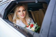 Piękna kobiety panna młoda z bukietem kwiaty i mężczyzny obsiadanie w samochodzie, przyglądającym za okno obrazy royalty free