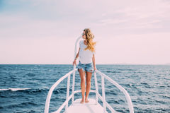 Piękna kobiety pozycja na nosie jacht przy pogodnym letnim dniem, popiółu rozwija włosy, piękny morze na tle Obraz Stock