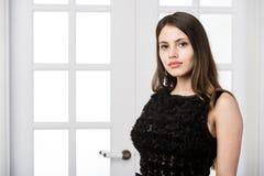 Piękna kobiety pozycja w czarnej sukni nad pracownianego loft domu wewnętrznymi drzwiami behind Fotografia Stock