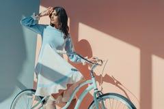 Piękna kobiety pozycja w modnej turkus sukni z długimi rękawami i obsiadanie na rowerowym i przyglądającym obrazy stock